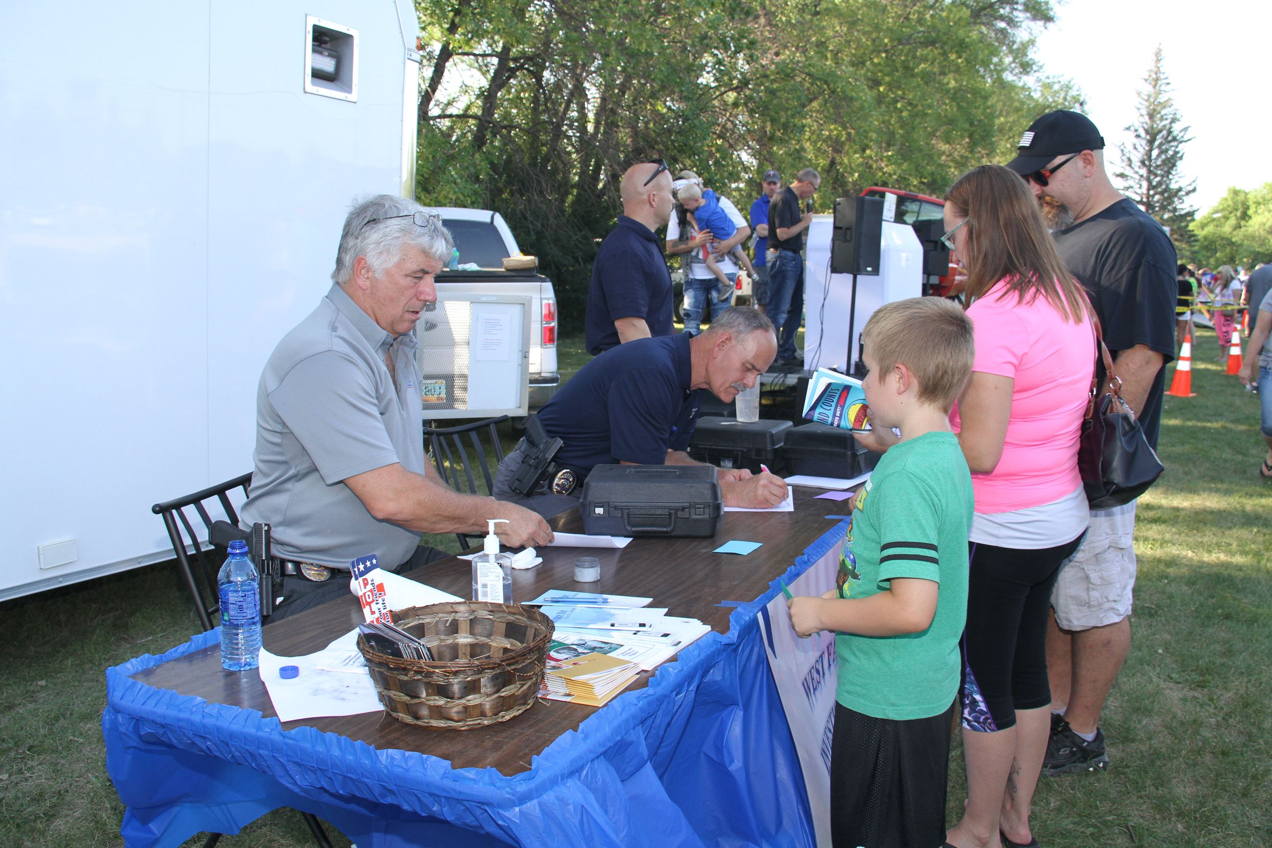 Attendees visit the West Fargo Police Department investigations table