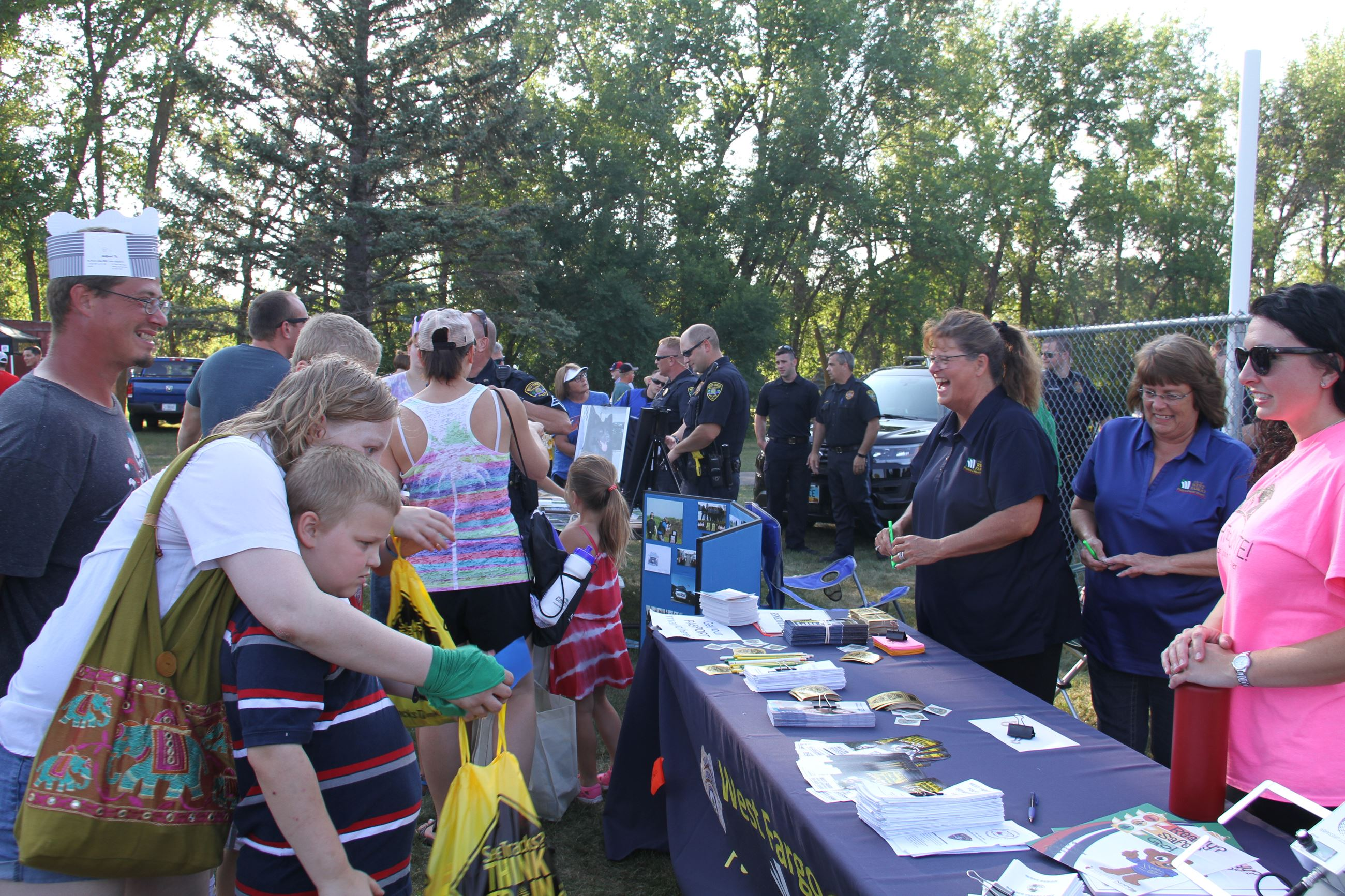 Attendees visit the West Fargo Police Department table to learn more about the department