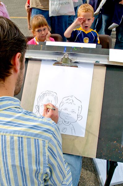 Street artist drawing cartoon of two children