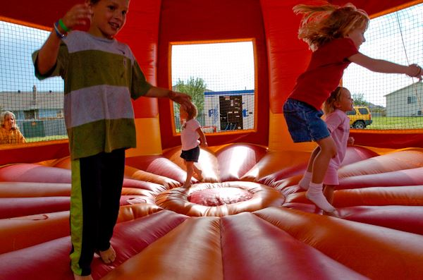 Four kids jumping in inflatable bounce house