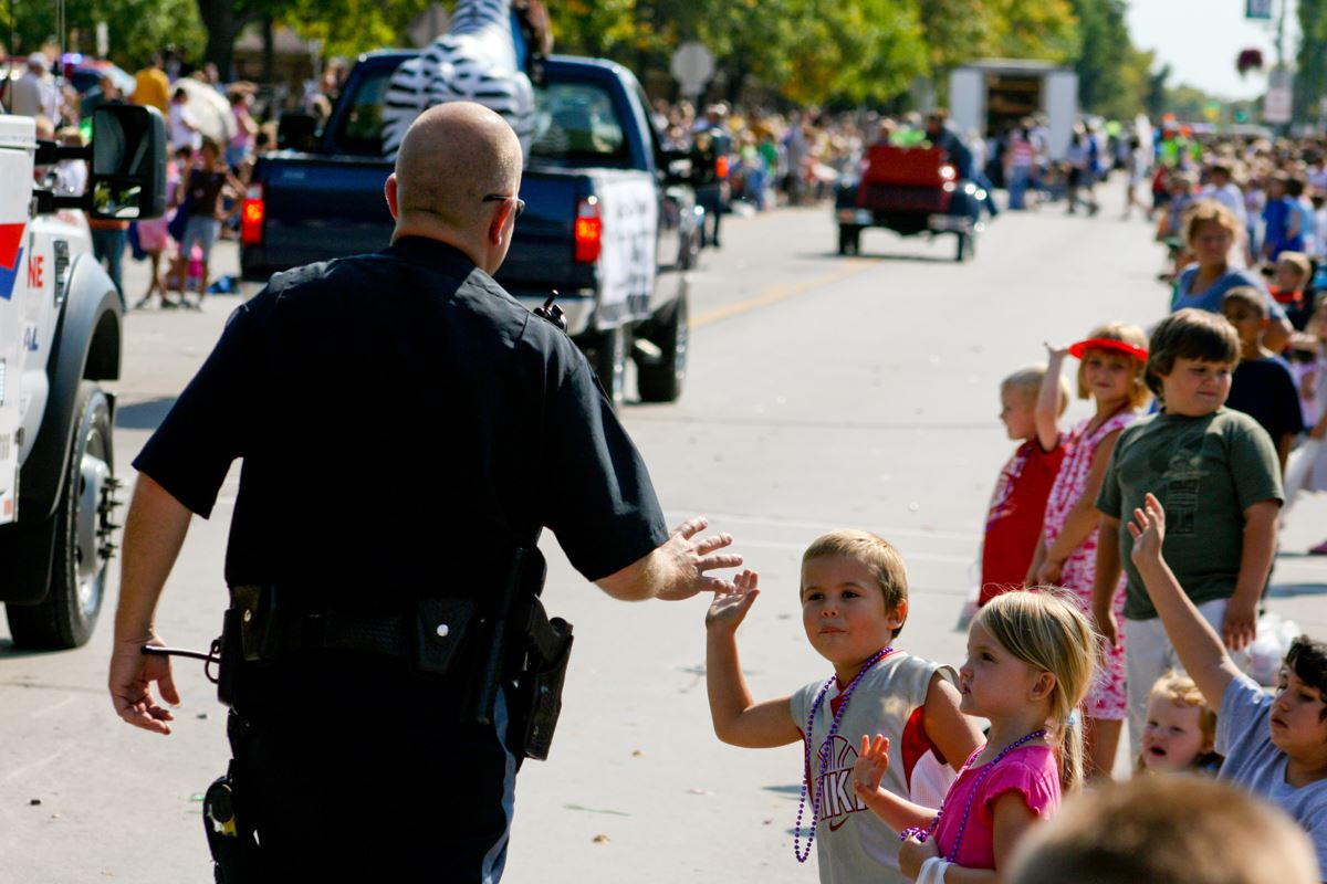 Kids lining up for parade receiving high fives from Police officer