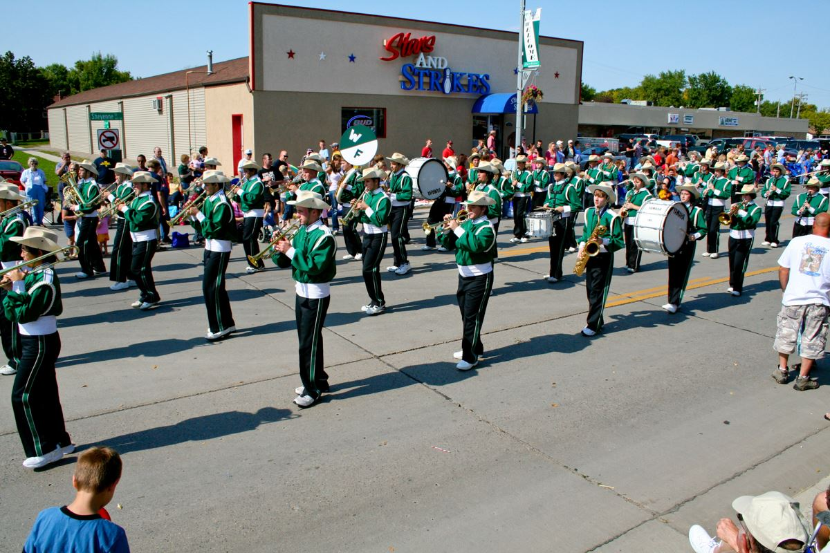 Image of high school band in green uniform performing in parade