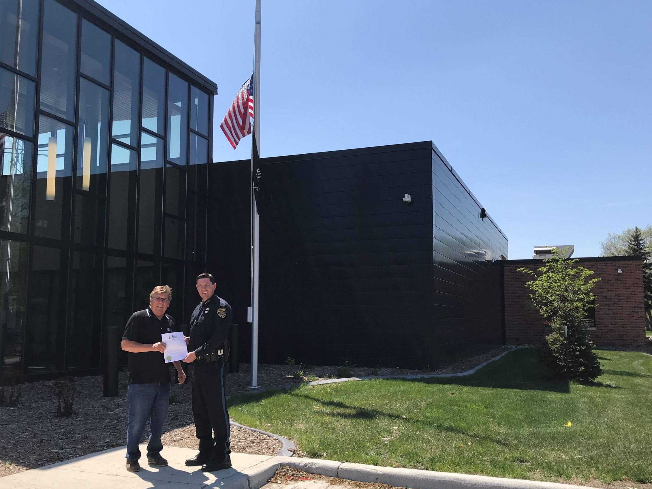 Mayor Mattern and Chief Janke pose in front of flags at half-staff in honor of Police Week in West F